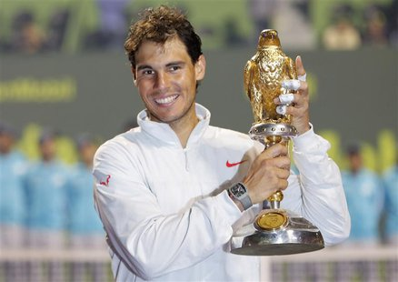 Rafael Nadal of Spain holds his trophy after winning the Qatar Open final tennis match in Doha January 4, 2014. REUTERS/Ahmed Jadallah