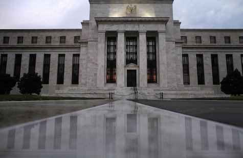 The facade of the U.S. Federal Reserve building is reflected on wet marble during the early morning hours in Washington, July 31, 2013.REUTE