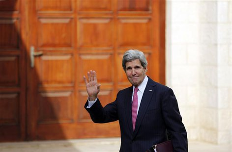 U.S. Secretary of State John Kerry waves upon arrival for a meeting with Palestinian President Mahmoud Abbas in the West Bank city of Ramall