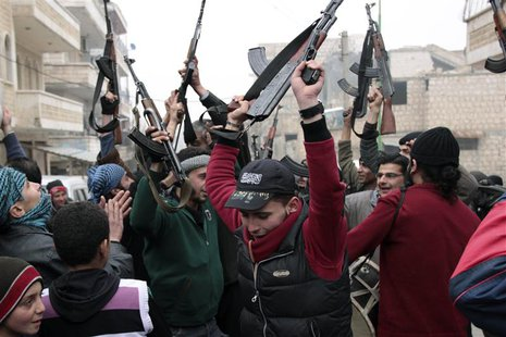 Free Syrian Army fighters cheer during an anti-Syrian regime protest in Maarat Al-Nouman, Idlib, January 3, 2014. Picture taken January 3, 2
