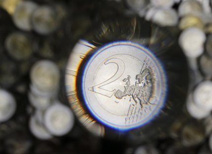 A two Euro coin is checked after being minted in the Austrian Mint (Muenze Oesterreich) headquarters in Vienna June 20, 2013. REUTERS/Leonha