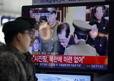 South Korean soldiers walk past a television showing reports on the execution of Jang Song Thaek, who is North Korean leader Kim Jong Un's u