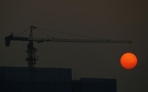 The sun sets behind a construction site in Guangzhou, Guangdong province, January 3, 2014. REUTERS/Alex Lee
