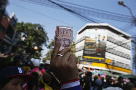 An anti-government protester holds up a Thai banknote to donate to anti-government protest leader Suthep Thaugsuban during a rally in centra