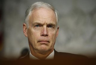 U.S. Senator Ron Johnson (R-WI) listens to Secretary of State Hillary Clinton respond to questions about the September attack on U.S. diplom
