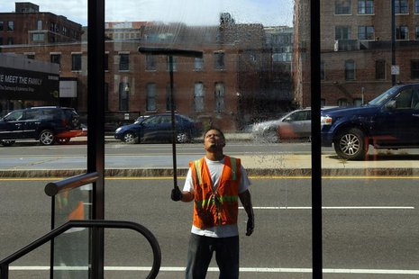 A worker washes the windows of a silver line bus station in Boston, Massachusetts August 12, 2013. REUTERS/Brian Snyder (