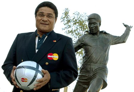 Portuguese soccer player Eusebio holds a soccer ball and poses in front of his statue at the entrance of the Luz Stadium in Lisbon in this J