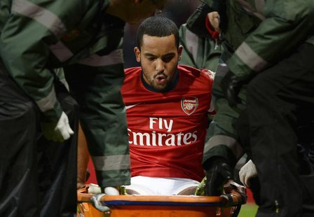 Arsenal's Theo Walcott is stretchered off the pitch during their English FA Cup soccer match against Tottenham Hotspur at the Emirates stadi