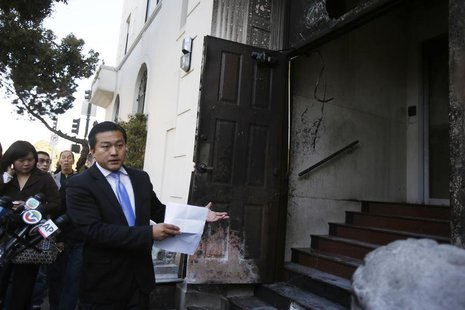 Wang Chuan, a spokesman for the Chinese consulate in San Francisco, points to a damaged door during a news conference after an unidentified