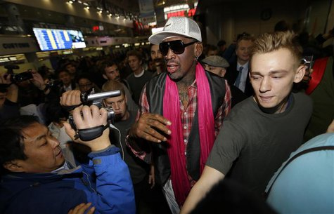 Former NBA basketball player Dennis Rodman (C) is surrounded by journalists as he arrives at the Beijing Capital International Airport to le