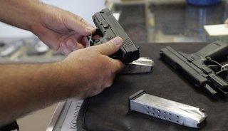 A customer inspects a 9mm handgun at Rink's Gun and Sport in the Chicago, suburb of Lockport, Illinois in this June 26, 2008 file photograph