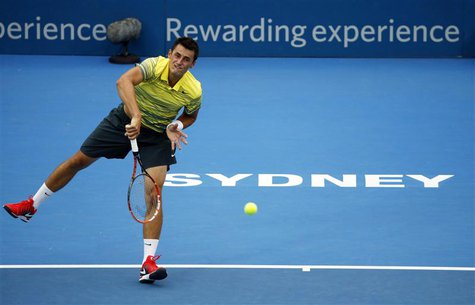 Bernard Tomic of Australia serves to Marcel Granollers of France during their first round match at the Sydney International tennis tournamen