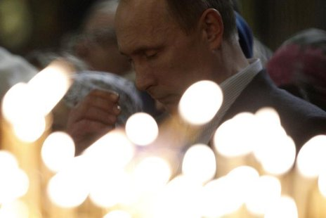 Russia's President Vladimir Putin gestures as he attends the Orthodox Christmas service at the Holy Face of Christ the Savior Church in the
