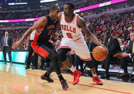 Dec 31, 2013; Chicago, IL, USA; Chicago Bulls small forward Luol Deng (9) is defended by Toronto Raptors shooting guard DeMar DeRozan (10) d