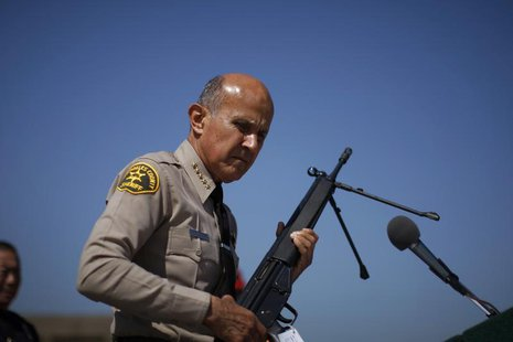 Los Angeles County Sheriff Lee Baca holds a .308 caliber semi-automatic rifle to be melted at the Los Angeles County Sheriff's Department's