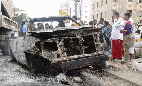 People gather around the vehicle of a Yemeni intelligence officer that was destroyed by a blast from an explosive device in the southern Yem
