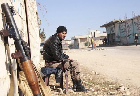 A rebel fighter guards a street to prevent members of the al Qaeda-affiliated Islamic State of Iraq and the Levant (ISIL) from entering Jaba