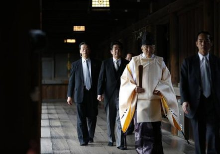 Japan's Prime Minister Shinzo Abe (2nd L) is led by a Shinto priest as he visits Yasukuni shrine in Tokyo December 26, 2013. CREDIT: REUTERS/TORU HANAI