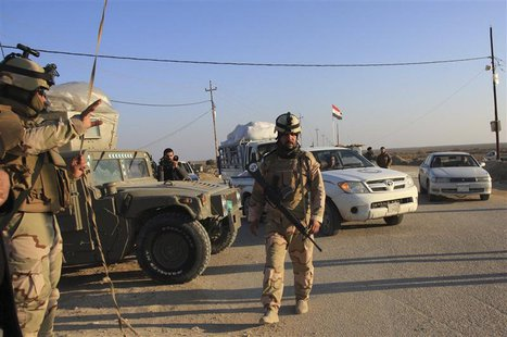 Iraqi soldiers stand guard at a checkpoint in Ein Tamarm, a town some 40 km (25 miles) west of Kerbala, January 7, 2014. REUTERS/Mushtaq Muh