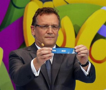 "FIFA Secretary General Jerome Valcke holds the slip showing ""Iran"" during the draw for the 2014 World Cup at the Costa do Sauipe resort in S"