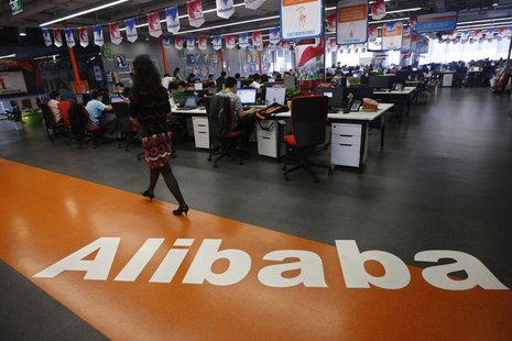 An employee walks past a logo of Alibaba Group at its headquarters on the outskirts of Hangzhou, Zhejiang province, in this May 17, 2010 fil