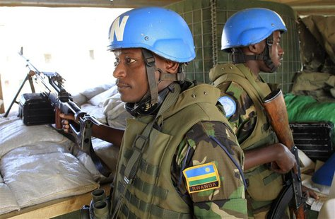 Soldiers from Rwanda serving under United Nations Mission in South Sudan (UNAMISS) hold their weapons as they keep watch from an observatory