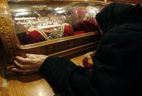 Trieza ,73, an Egyptian Christian grieves while kissing a glass capsule containing cloth belonging to Christian martyrs in the Coptic Orthod