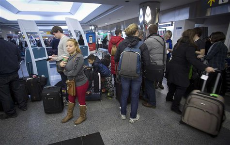 People line up for information about their flights at La Guardia airport in New York January 6, 2014. REUTERS/Carlo Allegri