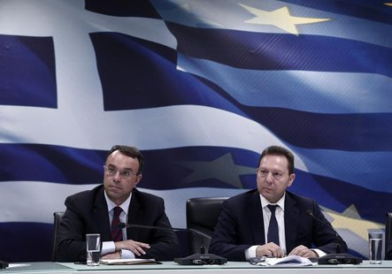 Greece's Finance Minister Yannis Stournaras (R) and Deputy Finance Minister Christos Staikouras listen to questions during a news briefing r