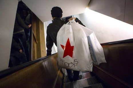 Shoppers ride the escalator at Macy's Herald Square in New York in this November 28, 2013 file photo. U.S. consumers shopped less on the fin
