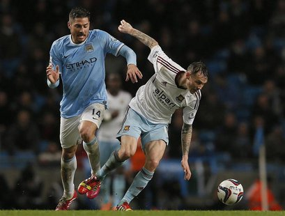 Manchester City's Javi Garcia (L) challenges West Ham United's Matt Taylor during their English League Cup semi-final first leg soccer match