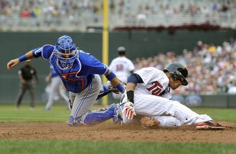 Toronto Blue Jays catcher J.P. Arencibia (L) tags out Minnesota Twins Pedro Florimon at home in the sixth inning of their MLB American Leagu