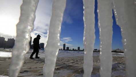 A man is framed by icicles as he walks along a beach in Chicago, Illinois, January 7, 2014.  CREDIT: REUTERS/JIM YOUNG (UNITED STATES - TAGS: ENVIRONMENT)