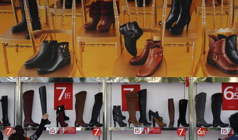 A customer picks up a shoe at a shop where posters advertising price discounts are hung, outside a department store in Beijing, October 23,