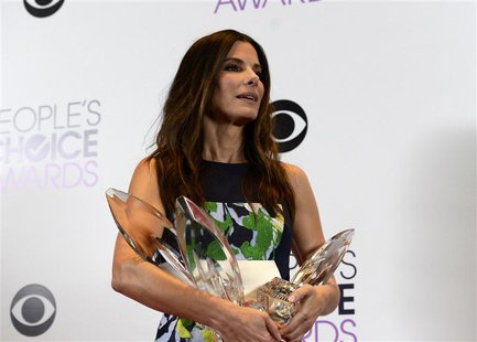 Sandra Bullock poses with the awards she won for favorite movie actress, favorite comedic movie actress and favorite dramatic movie actress