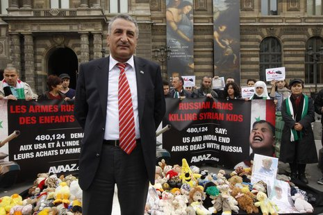 Syrian opposition member Dr. Kamal al-Labwani stand by a banner and children's stuffed toys at a demonstration near the Louvre Museum in Par