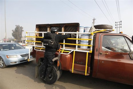 A police officer searches a vehicle at a checkpoint as security increases after a bomb attack, at Abu Ghraib district in west of Baghdad Jan