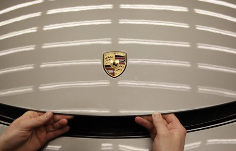 Worker closes engine bonnet of a new Porsche 918-Spyder sports car at the production line of the German car manufacturer's plant in Stuttgar