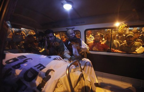 Relatives of Pakistan's Crime Investigation Department (CID) Chief Chaudhry Aslam sit in an ambulance with his body outside Jinnah Postgradu