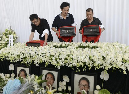 The fathers of Liu Yipeng, Wang Linjia and Ye Mengyuan, the three girls who died in the Asiana Airlines crash, carry the ashes of their daug