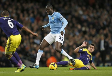 Manchester City's Yaya Toure (C) is challenged by Swansea's Pablo Hernandez during their English Premier League soccer match at the Etihad s