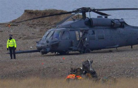 A police officer stands by a Pave Hawk helicopter, at the scene of a helicopter crash on the coast near the village of Cley next the Sea in Norfolk, eastern England January 8, 2014. CREDIT: REUTERS/TOBY MELVILLE