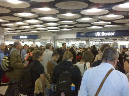 Travellers queue to be processed by UK Border Agency immigration control officers at Heathrow airport's Terminal 5 in London May 20, 2012. P