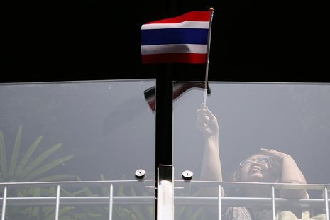 A woman waves a flag as she joins other anti-government protesters gathering in Bangkok's business district January 8, 2014. REUTERS/Damir S