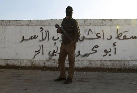 "A Free Syrian Army fighter carries his weapon as he stands in front of graffiti that reads ""Daesh (Islamic State of Iraq and the Levant ) do"