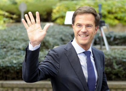 The Netherlands' Prime Minister Mark Rutte waves to the media upon arriving at a European Union leaders summit at the EU council headquarter