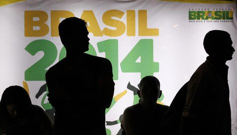 People are silhouetted in front of an advertisement of the Brazil 2014 FIFA Soccer World Cup as they wait for a bus in Recife June 21, 2013.