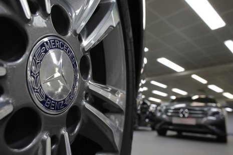 A company logo is seen on a wheel in front of Mercedes-Benz A-class cars displayed in a dealership of German car manufacturer Daimler in Par