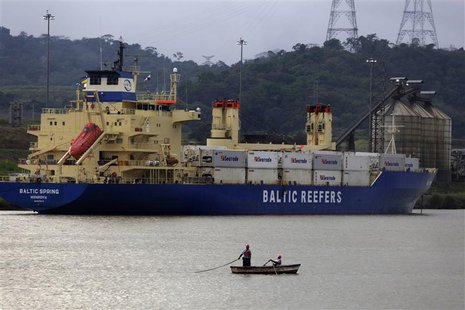 Panama workers are seen in a boat next to a cargo ship in the pacific side of the Panama Canal in Panama City January 8, 2014. REUTERS/ Carl