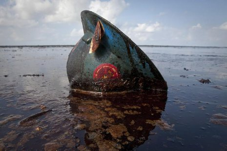 A hard hat from an oil worker lies in oil from the Deepwater Horizon oil spill on East Grand Terre Island, Louisiana June 8, 2010. REUTERS/L